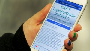 Kännykkä naisen kädessä, ruudulla näkyy Facebookin Käpy ry -ryhmä