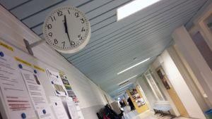 Koulun käytävä ja kello seinällä.