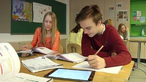 Kaksi oppilasta koulutehtävien äärellä.