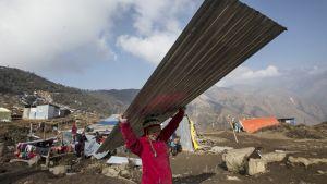 Nepalilainen tyttö kantaa aaltopeltiä päänsä yläpuolella. Tytöllä on kirkkaanpunainen takki ja pipo. Taustalla näkyy vuoristoista maisemaa ja väliaikaiselta näyttäviä rakennelmia. Kauempana pieni joukko ihmisiä on aaltopeltikasan luona.