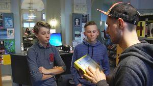 Mies esittelee kirjaa kahdelle pojalle kirjastossa.
