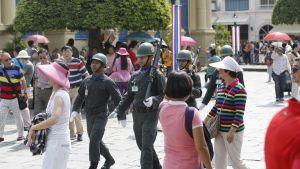 Kolme aseistettua, kypäräpäistä sotilasta marssiin kesäasuisten turistien joukon halki.