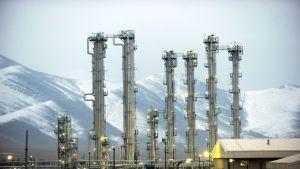 Lumisia vuoria vasten kohohoavia ydinlaitoksen torneja