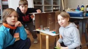 Pojat esittelevät itse rakentamaansa pahvitaloa.