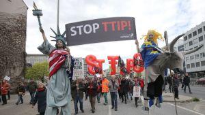 """Vapaudenpatsaaksi pukeutunut mies ja EU:ta symboloiva nainen kantavat kylttiä, jossa lukee """"Stopp TTIP!"""" Taustalla muita mielenosoittajia lippuineen."""