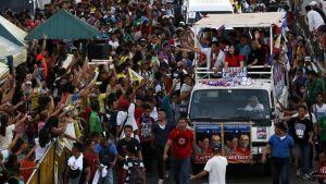 Duterte kampanjaväkineen kuorma-auton lavalla kurottelevan väkijoukon keskellä.