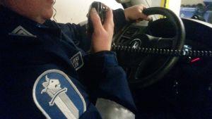 Poliisi puhuu käsipuhelimeen poliisiautossa.