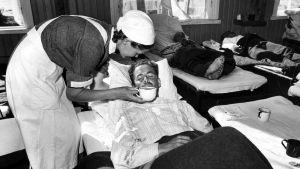 Lotta hoitaa vaikeasti haavoittunutta sotilasta sotasairaalassa jatkosodan aikana.