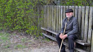 mies istuu pihapenkillä