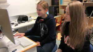 kaksi nuorta tyttöä istuu tietokoneruudun edessä. He editoivat videohaastattelua.