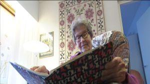 Aune Kulmala lukemassa kirjaa.