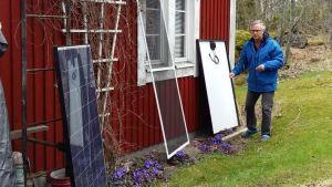 Omakotitalon takapihalla mies ja aurinkopaneeli.