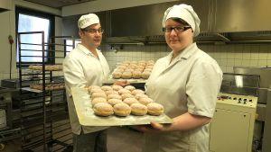 Kaksi leipuria käsissään pellilliset munkkeja