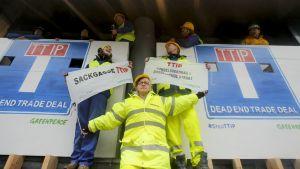 Greenpeacen aktivisteja TTIP-neuvotteluja vastustavien kylttien kanssa.