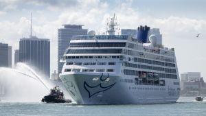 Vaalea risteilyalus etenee Miamin edustalla. Vieressä kulkeva hinaaja ruiskuttaa vettä kaaressa sivulle. Taustalla näkyy Miamin pilvenpiirtäjiä.