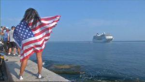 Yhdysvaltain lippuun kääriytynyt nainen seuraa risteiljän saapumista meren rannalla. Taustalla näkyy muutakin yleisöä.