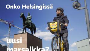 Helsingin kaupunkipyörä, koeajon suorittanut toimittaja Mikko Rita ja Mannerheimin patsas Helsingin keskustassa.