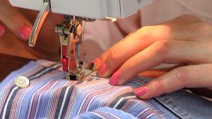 Nainen ompelee ompelukoneella.