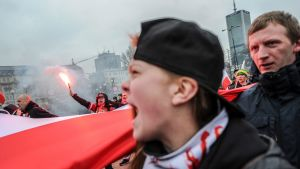 Lippalakkiin pukeutunut nainen huutaa äärioikeistolaisten mielenosoituksessa Puolan Varsovassa. Mielenosoittajat kantavat palavia soihtuja ja huutavat iskulauseita.