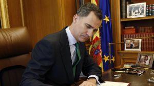 Kuningas Felipe istuu tummassa puvussa vihreä kravatti kaulassaan nahkatuolilla sävyltään vaalearuskeassa huoneessa ja allekirjoittaa edessään kirjoituspöydällä olevan asiakirjan. Hänen ilmeensä on vakava. Taustalla ovat Espanjan ja EU:n liput ja kirjahylly, jossa on myös valokuvia. Pöydällä on rivissä kyniä ja valokuva kuninkaasta vaimonsa ja lapsensa kanssa,