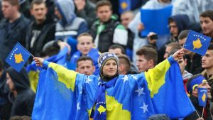 Poika pukeutuneena Kosovon lippuun.