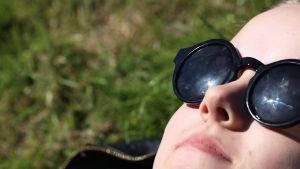 Nainen ottaa aurinkoa aurinkolasit päässään.