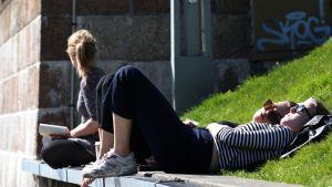 Naiset makaavat aurinkoisella nurmikolla.
