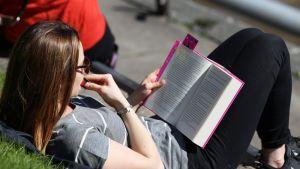 Nainen lukee kirjaa aurinkoisessa säässä.