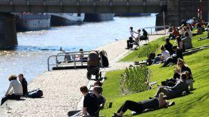 Ihmisiä aurinkoisessa Aurajoen rannassa.