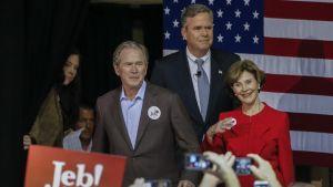 George, Jeb ja Laura Bush lavalla Yhdysvaltain lipun edessä. Edessä kannattaja heiluttama Jeb!-kyltti.