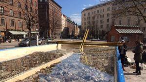 Installaatio, jossa suuri risti pilkistää jätelavalta.