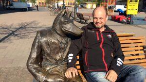 Perussuomalaisten kansanedustaja Kari Kulmala istuu susipatsaan vieressä Joensuun torilla.