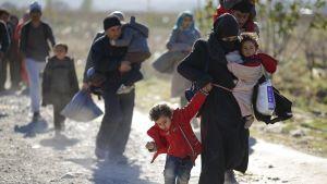 Nainen kantaa lasta sylissä ja taluttaa toista kädestä, takana muita ihmisiä, muun muassa mies lapsi sylissä.