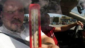 Teemu Kahila esittelee lämpömittaria kuumassa autossa.