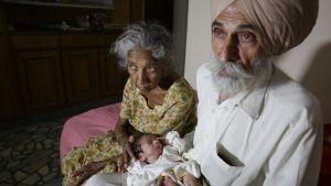 70-vuotias Dalwinder Kaur ja hänen 79-vuotias miehensä Mohinder Singh Gill ensimmäisen lapsensa, Armanin kanssa.