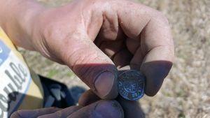 Flaamilainen kolikko miehen käsissä