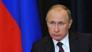 Putin katsoo vakavana kuvan vasenta reunaa kohti. Hänellä on tumma puku, tummanpunainen kravatti, jossa on sinistä kuviota. Taustalla näkyy Venäjän lippu.