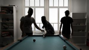 Nuoret turvapaikahakijat pelaavat biljardia vastaanottokeskuksen ikkunan äärellä.