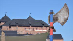 Hämeen linna taustalla, etualalla taisteluväline
