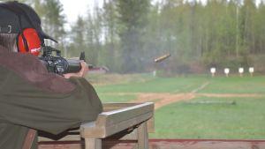 Reserviläinen ampuu maalitauluun rynnäkkökiväärillä.