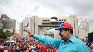 Presidentti Maduro käsi ojossa, taustalla ihmisjoukko