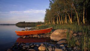 Saimaan rannalla soutuvene auringon laskiessa.
