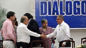 Kolumbian hallituksen neuvottelija Humberto de la Calle kättelee Farc-sissien johtohahmoa Rodrigo Grandaa (oikealla) rauhanneuvotteluissa Havannassa 12.5. 2016.