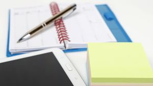 Kalenteri, puhelin ja muistilappuja.