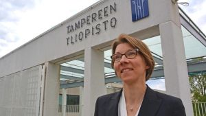 Tampereen yliopiston professori Eija Vinnari yliopiston sisäänkäynnin edessä.