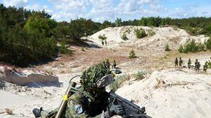 sotilas rynnäkkökivääreineen hiekkadyynillä