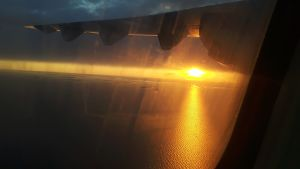 Auringonlasku Perämerellä lentokoneen ikkunasta katsottuna.