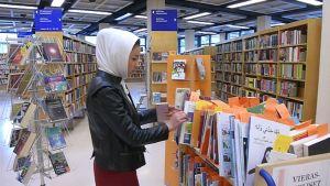 Fereshte Khodadadi selailee kirjoja Porin kirjastossa