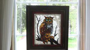 Lasinen pöllötaulu ikkunalla