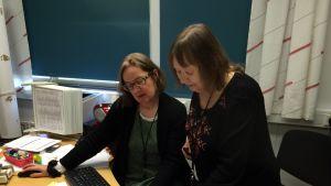 Lukion apulaisrehtori Eeva Vallittu ja Utsjokisuun koulun rehtori Marjatta Krogerus tutkivat ylioppilaskirjoitusten tuloksia.